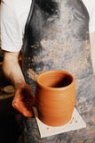 Hand of potter with jug Royalty Free Stock Images