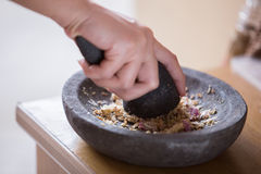 Hand pounding herbs on a traditional pounder Royalty Free Stock Image