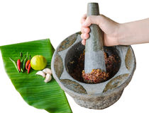 Hand pounding shrimp paste chilli sauce in mortar. With ingredient on banana leaf -thai style Royalty Free Stock Photo