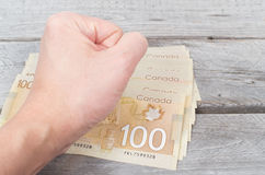 Hand pounding on a stack of bank notes. On a wooden table Stock Image