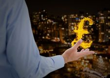 Hand with pounds fire icon over in front of the city at night. Digital composite of hand with pounds fire icon over in front of the city at night Royalty Free Stock Images