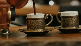 Hand pouring black coffee from turk into coffee cup stock video footage