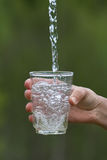 Hand pouring clean natural water into a glass royalty free stock photography