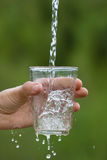 Hand pouring clean natural water royalty free stock images