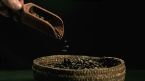 Hand pouring coffee beans from wooden spoon to basket Royalty Free Stock Photography