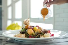 Hand pouring cream sauce into mixed fruits salad in the restaurant stock photography