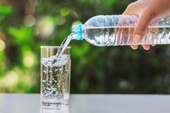 hand pouring drinking water into glass form bottle Royalty Free Stock Photos