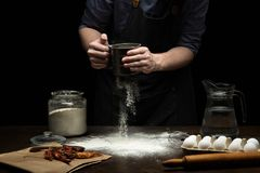 Hand pouring flour to make a dough. On wooden table royalty free stock photo