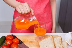 Hand pouring a fresh orange juice in a glass Royalty Free Stock Photos