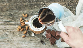 Hand pouring freshly brewed coffee from cezve - coffee pot - to Royalty Free Stock Photo