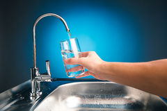 Hand pouring a glass of water from filter tap. Blue background Royalty Free Stock Photos