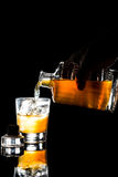 Hand pouring a glass of whiskey on the rocks against a dark background Stock Image