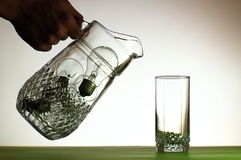 Hand pouring from jug of light bulbs into glass Stock Photos