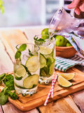 Hand is pouring from jug of mohito cocktail drink Royalty Free Stock Photo