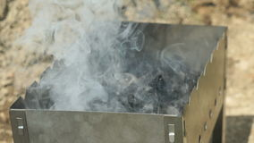 Hand pouring lighter fluid coals in the brazier stock video footage