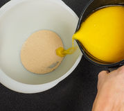 Hand pouring melted butter into a white bowl with dry yeast Royalty Free Stock Image