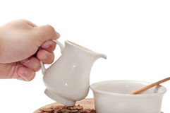 Hand pouring milk in the bowl with chocolate cornflakes Royalty Free Stock Image