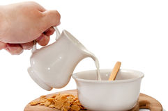 Hand pouring milk in the bowl with cornflakes Stock Image