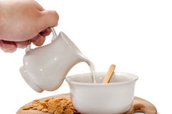 Hand pouring milk in the bowl with cornflakes Stock Photo