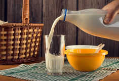 Hand pouring milk into glass. Man's hand pouring milk from plastic bottle into glass. Two plastic bowls and wicker basket over checked table-napkin and wooden stock images