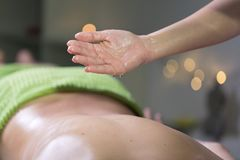 Hand pouring oil for massage in spa studio. Oil drop royalty free stock photos