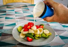 Hand pouring pot of fresh cream over Banannas, Strawberries and Avocado on white plate. Hand pouring pot of fresh cream over Banannas, Strawberries and Avocado royalty free stock photo