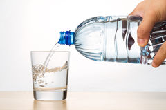 Hand pouring refreshing natural mineral water from bottle into g Royalty Free Stock Photography