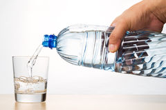 Hand pouring refreshing natural mineral water from bottle into g Stock Photography