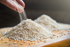 Hand pouring rice on pile of white rice on wooden table background, metaphor ingredient, nutrition, carbohydrate food concept, se. Lective focus royalty free stock photos