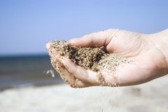 Hand pouring sand. A hand pouring some beach sand, close up, detailed, motion blur Stock Images