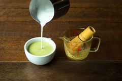 Hand pouring steam milk on hot matcha green tea latte Royalty Free Stock Photography