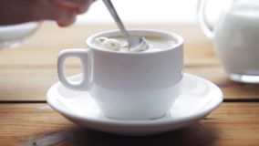 Hand pouring sugar by teaspoon into coffee cup stock footage