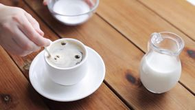 Hand pouring sugar by teaspoon into coffee cup. Unhealthy eating and drinks concept - hand with teaspoon pouring sugar into coffee cup on wooden table stock video