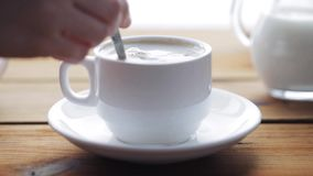Hand pouring sugar by teaspoon into coffee cup. Unhealthy eating and drinks concept - hand with teaspoon pouring sugar into coffee cup on wooden table stock footage