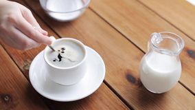 Hand pouring sugar by teaspoon into coffee cup. Unhealthy eating and drinks concept - hand with teaspoon pouring sugar into coffee cup on wooden table stock video footage
