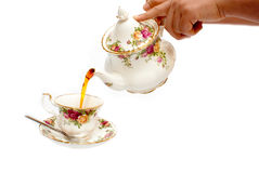 Hand pouring tea from a china teapot Stock Photos
