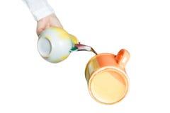 Hand pouring tea from teapot Stock Photos