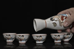 Hand pouring from a tiny antique jug Stock Photography