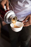 Hand pouring Traditional Indian masala tea into white ceramic cu Royalty Free Stock Photography