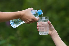 Hand pouring water from bottle into glass on nature background Stock Photography