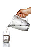 Hand pouring water from glass jug. Hand pouring water from jug to glass against white background Stock Images