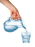 Hand pouring water from glass pitcher Royalty Free Stock Images