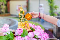 Hand pouring water to emerald buddha with pink lotus on Songkran Festival. Bangkok, Thailand - April 13, 2017 : Hand pouring water to emerald buddha with pink Stock Photography