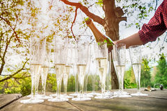 Hand pouring wine into flute glasses of champagne Stock Image