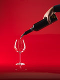 Hand pouring wine in glass from bottle Stock Photography