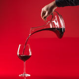 Hand pouring wine in glass from decater Royalty Free Stock Image