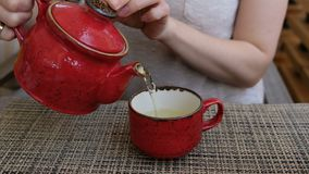 Hand that pours chinese green tea from ceramic kettle to smal cup, close up stock video footage