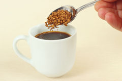 Hand pours granulated coffee from spoon in a coffee cup Royalty Free Stock Photography