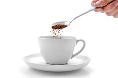 Hand pours instant coffee from a spoon in a coffee cup. Isolated on white background Royalty Free Stock Images