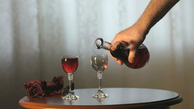 Hand pours a liqueur in wine glasses from a carafe. The hand of the barman pours the liqueur in wine glasses from the carafe stock video